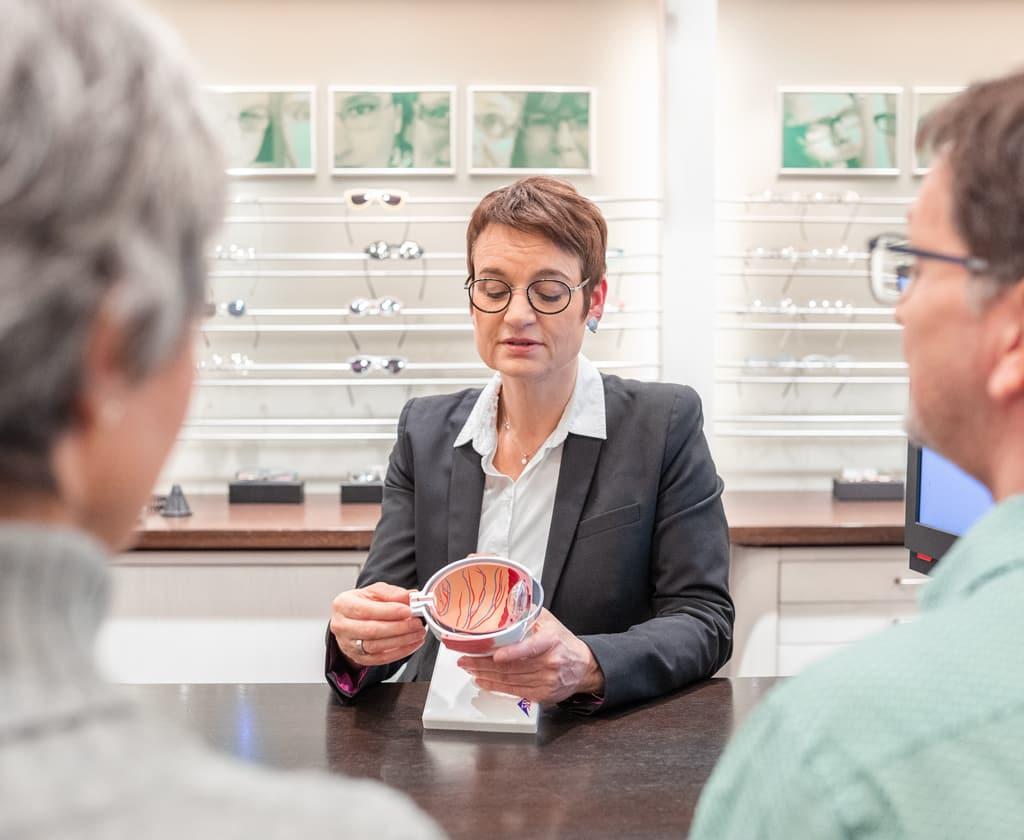 Augenoptiker erklärt Kunden die Funktion der Netzhaut