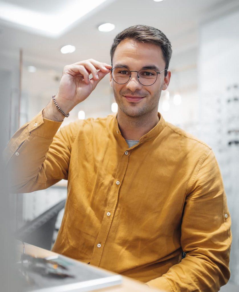 Mann mit Brille schaut in den Spiegel