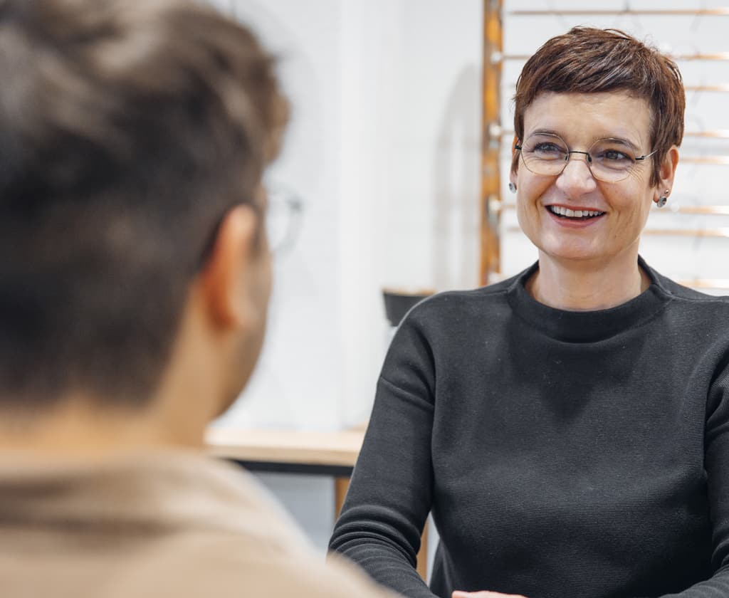 Optikerin mit Brille im Gespräch mit Ihrem Kunden