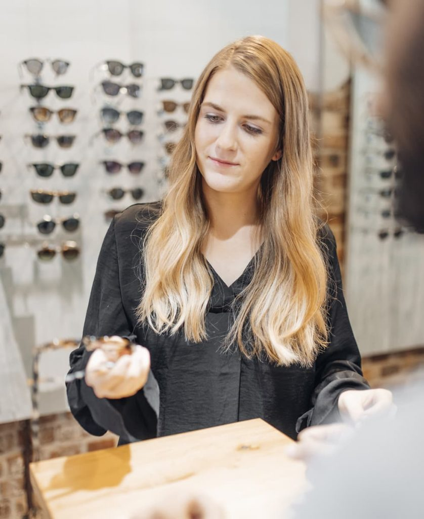 Frau hält eine neue Brille in der Hand