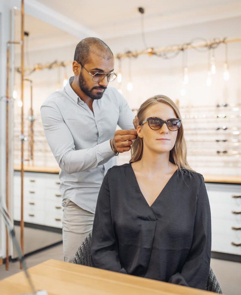 Optiker passt neue Sonnenbrille bei einer Kundin an
