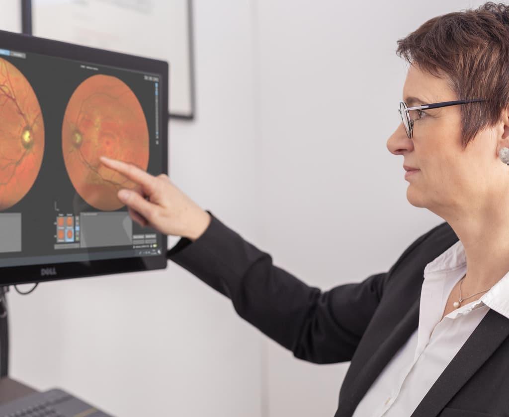 Optikerin erklärt am Monitor Netzhautscreening