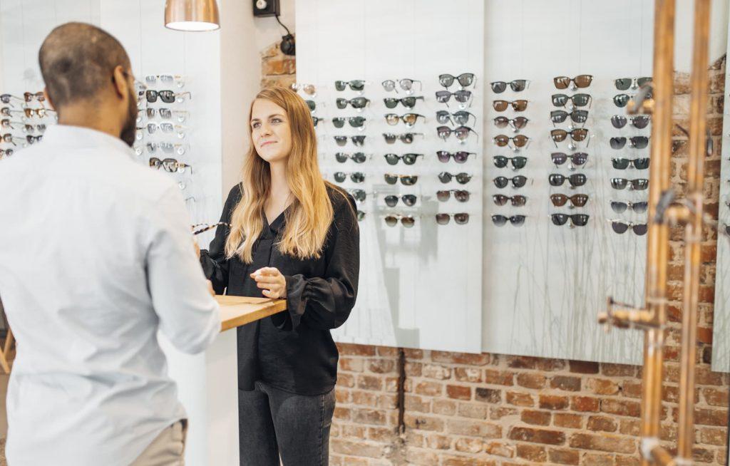 Frau kauft eine Sonnenbrille beim Optiker