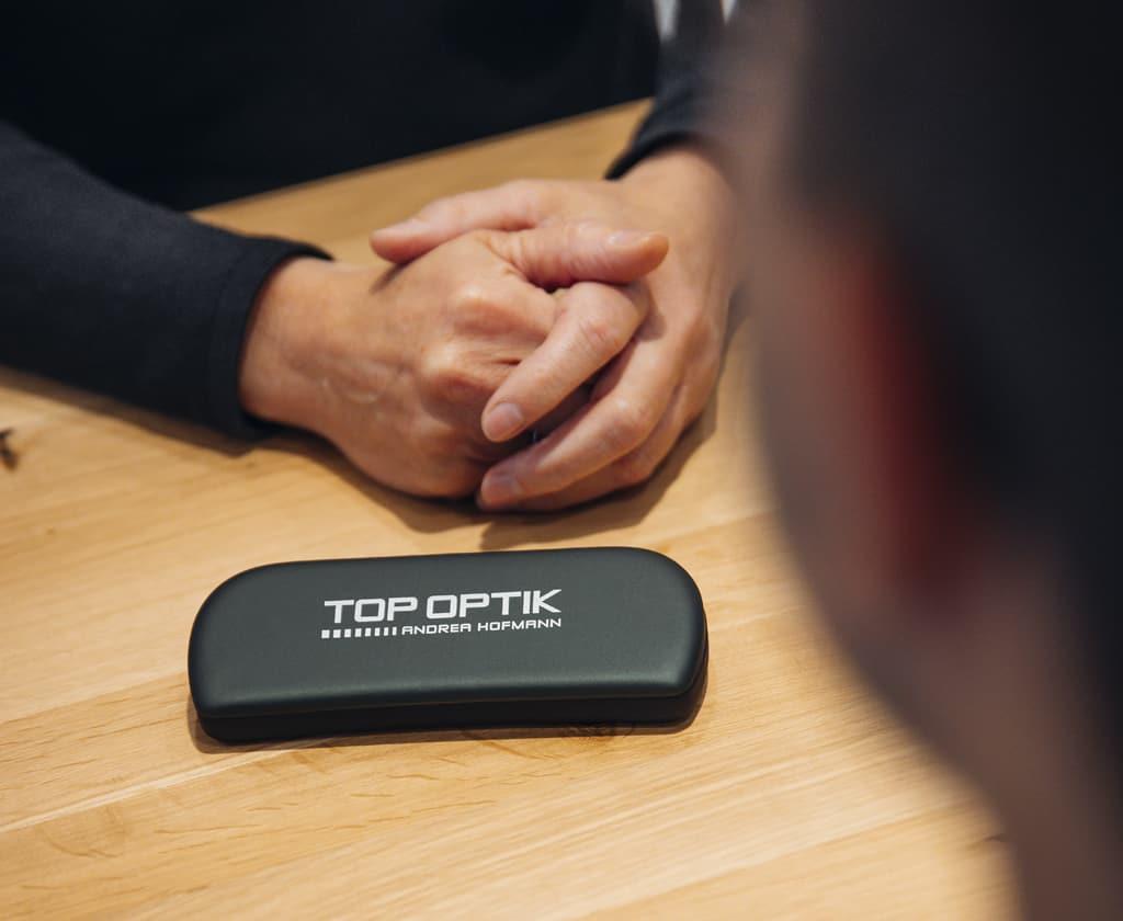 Ein Brilenetui mit TOP OPTIK Schriftzug liegt auf dem Tisch