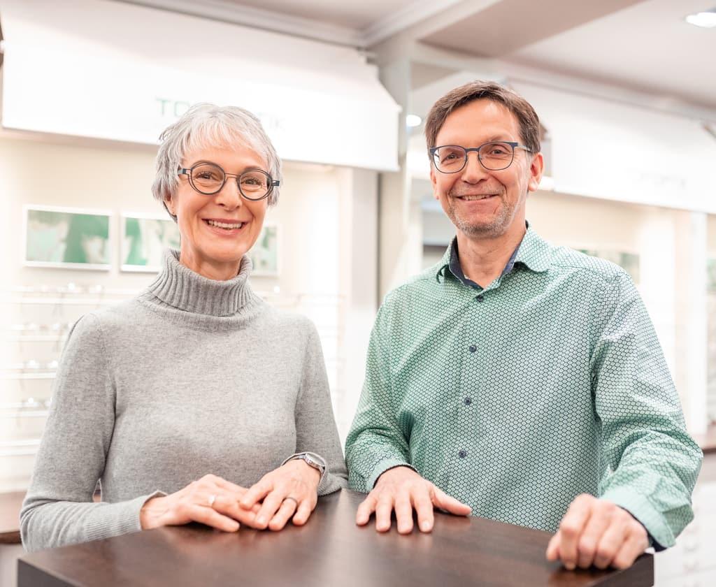 Ehepaar mit Brille schaut in die Kamera